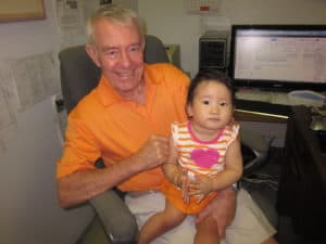 Realtor Tom Delmore & Granddaughter Madison busy working on real estate in matching orange outfits