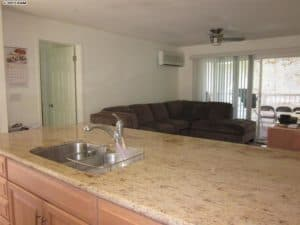 Granite counter top in open kitchen flows into living room in this newly remodeled condo.